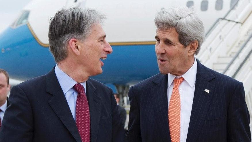 U.S. Secretary of State John Kerry, right, is greeted by British Foreign Secretary Philip Hammond in London, England, Saturday, March 21, 2015, for a meeting about the recently concluded round of negotiations with Iran over Iran's nuclear program.   (AP Photo/Brian Snyder, Pool)