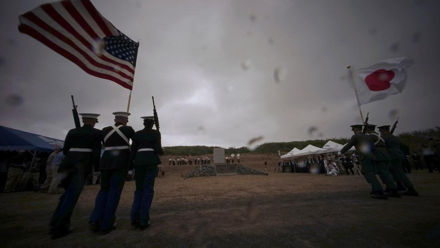The color guard of the United States Marines and Japan Self Defense Force hold the flags of the U.S. and Japan during a ceremony commemorating the 70th anniversary of the Battle of Iwo Jima, now known as Ioto, Japan, Saturday, March 21, 2015. The battle is one of WWII's bloodiest and most iconic battles.  (AP Photo/Eugene Hoshiko)