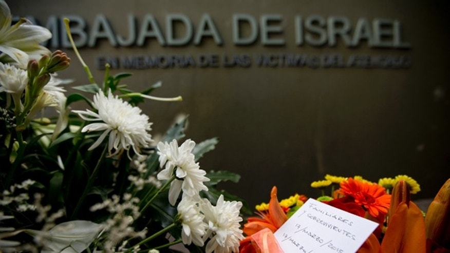 "A piece of paper reading in Spanish ""Relatives and survivors, March 17, 2015, March 17, 1992"" is placed on floral arrangements that sit where the Israeli Embassy used to be, during an act to commemorate the 23rd anniversary of the bomb attack that destroyed the Israeli Embassy building killing 22 people in Buenos Aires, Argentina, Tuesday, March 17, 2015. (AP Photo/Natacha Pisarenko)"