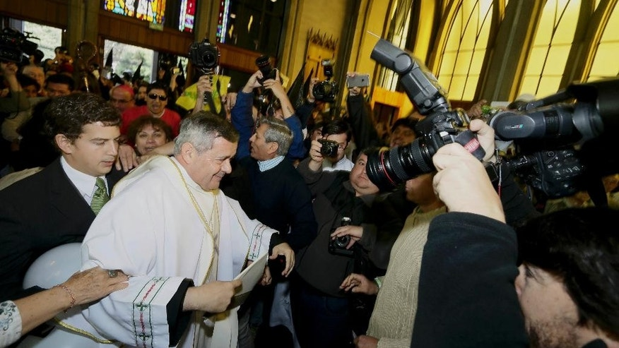 Protestors, background left, shout as Rev. Juan Barros, center left,  enters the cathedral for the ceremony to assume as bishop in Osorno, southern Chile, Saturday, March 21, 2015.  Barros was ordained amid protests by sex-abuse victims who accuse him of covering up crimes his mentor  Rev. Fernando Karadima  whom the Vatican has sanctioned for abusing young boys.(AP Photo/Mario Mendoza Cabrera) CHILE OUT - NO USAR EN CHILE