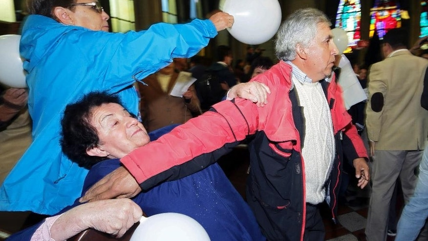 A supporter of Rev. Juan Barros, right, tries to restrain protestors as Barros, not seen,  enters the cathedral for his ordination ceremony as bishop in Osorno, Chile, Saturday, March 21, 2015.  Barros was ordained amid protests of people that accuse him of covering up sexual abuse committed by his mentor  Rev. Fernando Karadima in the 1980s and '90s.(AP Photo/Mario Mendoza Cabrera) -  CHILE OUT - NO USAR EN CHILE