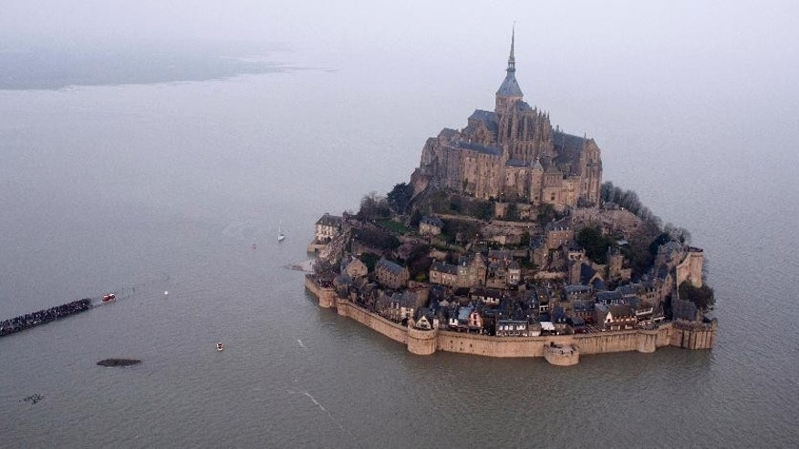 "An aerial view as a high tide submerges a narrow causeway leading to the Mont Saint-Michel, on France's northern coast, Saturday, March 21, 2015. A supertide has turned France's famed Mont Saint-Michel into an island and then retreated out of sight, delighting thousands of visitors who came to see the rare phenomenon. The so-called ""tide of the century"" actually happens every 18 years (AP Photo) FRANCE OUT"