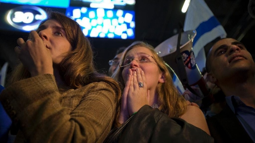 In this Wednesday, March 17, 2015 photo, Zionist Union party supporters react to exit polls at the party's election headquarters in Tel Aviv, Israel. Opinion polls published on the eve of Tuesday's election had shown the center-left Zionist Union slightly ahead of Prime Minister Benjamin Netanyahu's hawkish Likud Party. But as the results trickled in on Wednesday, they showed Likud with a shocking lead that has all but guaranteed Netanyahu a third consecutive term. (AP Photo/Ariel Schalit)