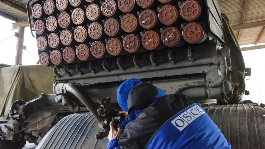 An OSCE monitor inspects Grad rocket launchers stored by pro-Russian rebels in the village of Novoamvrosiivske, eastern Ukraine, Friday, March 20, 2015. The OSCE was tasked to verify the pullback of heavy weapons by the Ukrainian government forces and the rebels in eastern Ukraine under a cease-fire deal. (AP Photo/Mstyslav Chernov)