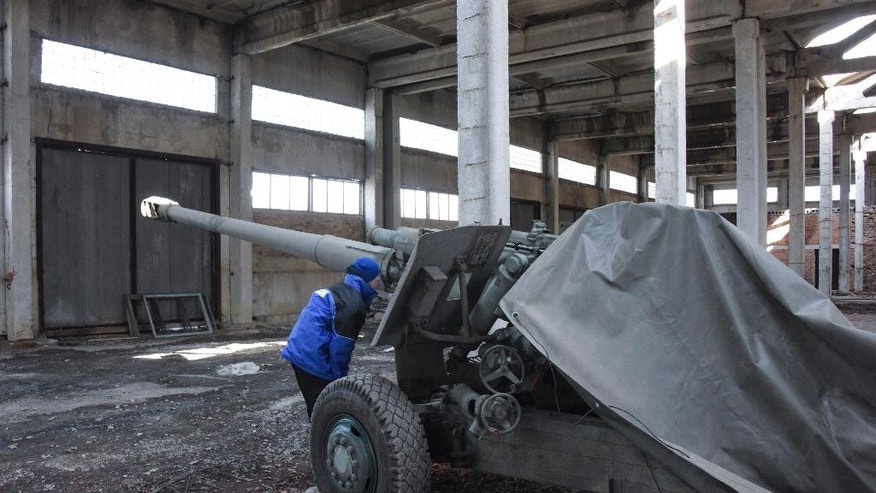 An OSCE monitor inspects a cannon stored by pro-Russian rebels in the village of Novoamvrosiivske, eastern Ukraine, Friday, March 20, 2015. The OSCE was tasked to verify the pullback of heavy weapons by the Ukrainian government forces and the rebels in eastern Ukraine under a cease-fire deal. (AP Photo/Mstyslav Chernov)