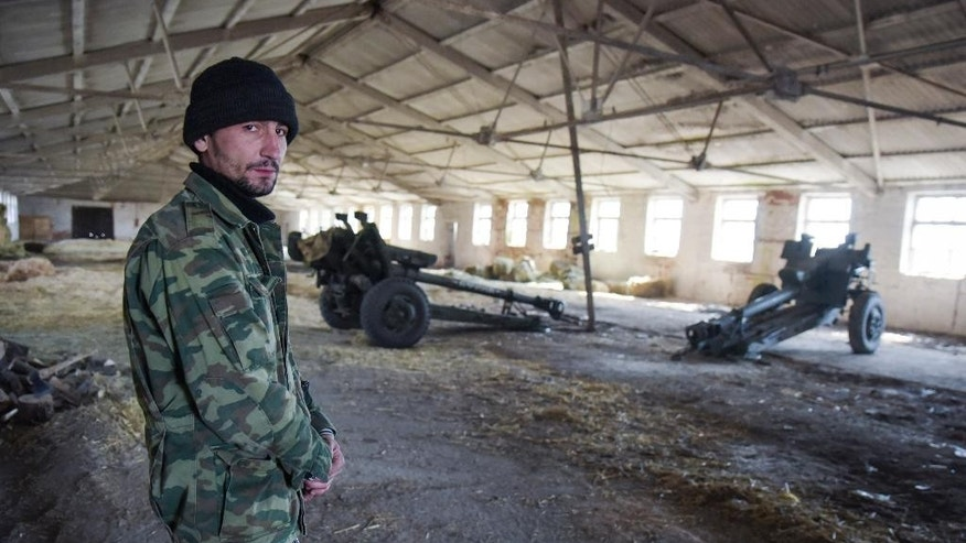 A pro-Russian rebel stands on guard in a storage for cannons in the village of Novoamvrosiivske, eastern Ukraine, Friday, March 20, 2015. The OSCE was tasked to verify the pullback of heavy weapons by the Ukrainian government forces and the rebels in eastern Ukraine under a cease-fire deal. (AP Photo/Mstyslav Chernov)