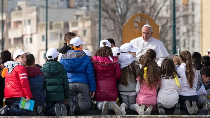 Pope Francis meets children during his visit to Scampia, suburb of Naples, Italy, Saturday, March 21, 2015. Pope Francis made an impassioned defense of the unemployed during a speech to people in the poor Neapolitan neighborhood of Scampia Saturday. (AP Photo/Andrew Medichini)