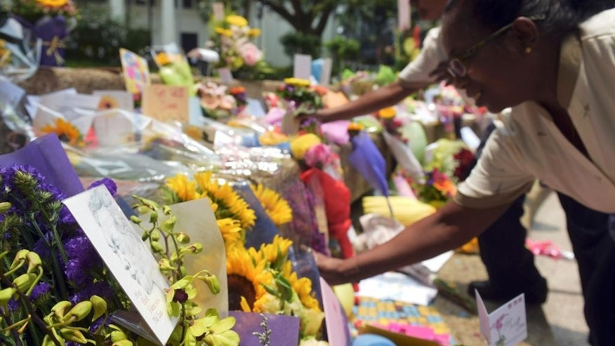 Well-wishers leave flowers at Singapore General Hospital where Singapore's 91-year-old founding father Lee Kuan Yew has been treated for the last six weeks, Saturday, March 21, 2015 in Singapore. The health of Lee has further deteriorated, the government said Saturday. (AP Photo/Joseph Nair)