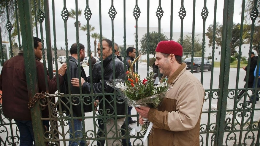 Tunisian man hands over flowers at the entrance gate of the National Bardo museum in Tunis, Tunisia, Saturday March 21, 2015.  The two extremist gunmen who killed 21 people at a museum in Tunis trained in neighboring Libya before caring out the deadly attack, a top Tunisian security official said. (AP Photo/Michel Euler)