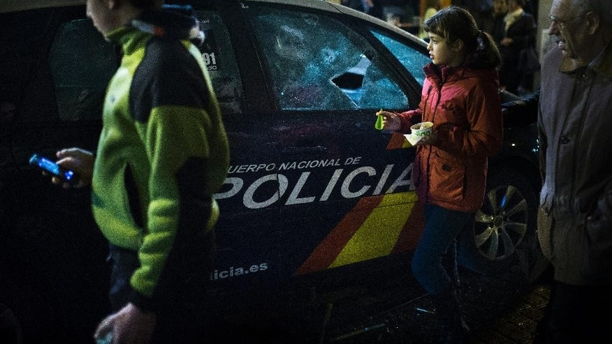 "EDS NOTE - SPANISH LAW REQUIRES THAT THE FACES OF MINORS ARE MASKED IN PUBLICATIONS WITHIN SPAIN - People pass by a police car broken by protestors during a ""Dignity March"" to protest against the Government in Madrid, Spain, Saturday, March 21, 2015. Thousands from different parts of Spain marched towards the Capital to join a large anti-austerity demonstration to express their anger at government financial cuts, its housing rights policies, and the high unemployment rates and to protest the Transatlantic Trade and Investment Partnership (TTIP) a proposed free trade agreement between the European Union and the United States. (AP Photo/Andres Kudacki)"