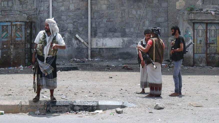 In this photo taken Wednesday, March 18, 2015, militiamen loyal to President Abed Rabbo Mansour Hadi check a pedestrian on a street in Aden, Yemen. The city is visibly expecting assault, whether from the forces of Hadi's rival, ousted President Ali Abdullah Saleh, who has allied himself with the Shite rebels, or from al-Qaida militants. Army and police forces loyal to Hadi and their allied militiamen patrol Aden's streets and man checkpoints at key locations. Tanks guard roads leading to the city and children are largely staying home from school. (AP Photo/Yassir Hassan)