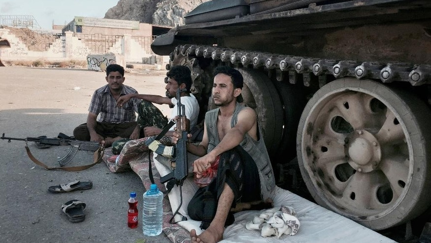 In this photo taken Saturday, March 21, 2015, members of a militia group loyal to Yemen's President Abed Rabbo Mansour Hadi, known as the Popular Committees, chew qat, Yemen's favorite drug, as they sit next to their tank, guarding a major intersection in Aden, Yemen. The city is visibly expecting assault, whether from the forces of Hadi's rival, ousted President Ali Abdullah Saleh, who has allied himself with the Shite rebels, or from al-Qaida militants. Army and police forces loyal to Hadi and their allied militiamen patrol Aden's streets and man checkpoints at key locations. Tanks guard roads leading to the city and children are largely staying home from school. (AP Photo/Hamza Hendawi)