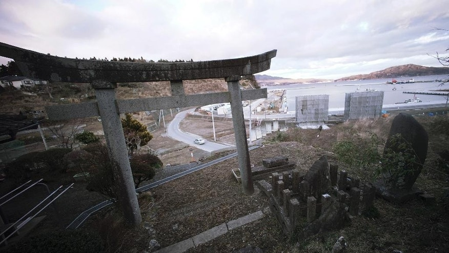 In this March 5, 2015 photo, a Shinto shrine gate remains standing on a hill as sea walls are being built in the waterfront area in Rikuzentakata, Iwate Prefecture, northeastern Japan. Four years after a towering tsunami ravaged much of Japan's northeastern coast, efforts to fend off future disasters are focusing on a nearly 400-kilometer (250 mile) chain of cement sea walls, at places nearly five stories high. (AP Photo/Eugene Hoshiko)