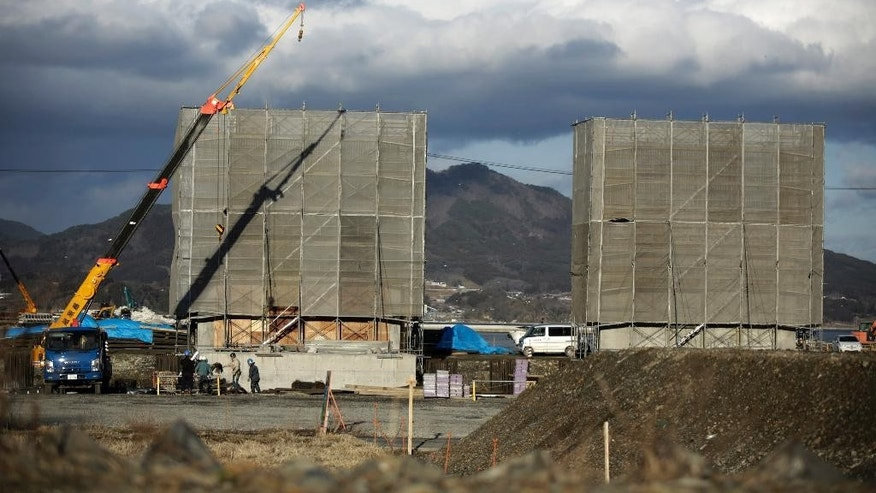 In this March 5, 2015 photo, workers build sea walls in Rikuzentakata, Iwate Prefecture, northeastern Japan. Four years after a towering tsunami ravaged much of Japan's northeastern coast, efforts to fend off future disasters are focusing on a nearly 400-kilometer (250 mile) chain of cement sea walls, at places nearly five stories high. (AP Photo/Eugene Hoshiko)