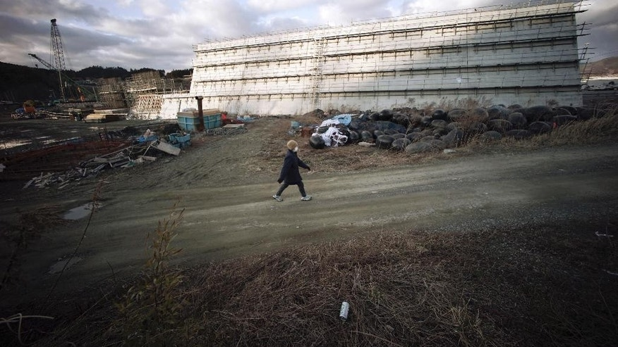 In this March 5, 2015 photo, a woman walks near sea walls being built in Rikuzentakata, Iwate Prefecture, northeastern Japan. Four years after a towering tsunami ravaged much of Japan's northeastern coast, efforts to fend off future disasters are focusing on a nearly 400-kilometer (250 mile) chain of cement sea walls, at places nearly five stories high. (AP Photo/Eugene Hoshiko)