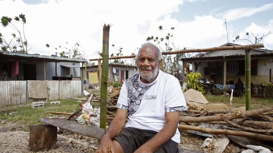 In this Saturday, March 21, 2015, photo, Lik Simelum poses in front of his kitchen, which was destroyed by Cyclone Pam this month on the island of Efate, Vanuatu. The 76-year-old has survived volcanos, landslides, earthquakes and cyclones, including Cyclone Pam, which struck Vanuatu this month, destroying thousands of homes. (AP Photo/Nick Perry)