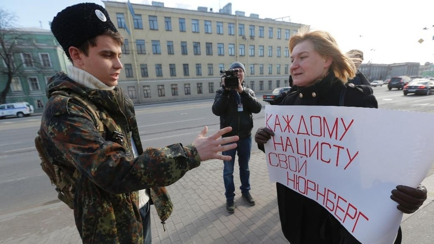 A Cossack argues with an Russia's anti-fascist activist, right, during  protest near the venue of the the International Russian Conservative Forum in St. Petersburg, Russia, Sunday, March 22, 2015. The poster reads ' To each fascist his Nuremberg'.  Nationalist supporters of Russian President Vladimir Putin brought together controversial far-right politicians from across Europe on Sunday in an effort to demonstrate international support for Russia and weaken European Union commitment to sanctions imposed on Russia over its role in Ukraine. (AP Photo/Dmitry Lovetsky)