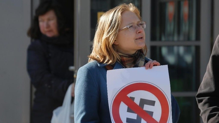 A Russian anti-fascist activist holds a poster during a  protest near the venue of the the International Russian Conservative Forum in St. Petersburg, Russia, Sunday, March 22, 2015. Nationalist supporters of Russian President Vladimir Putin brought together controversial far-right politicians from across Europe on Sunday in an effort to demonstrate international support for Russia and weaken European Union commitment to sanctions imposed on Russia over its role in Ukraine. (AP Photo/Dmitry Lovetsky)