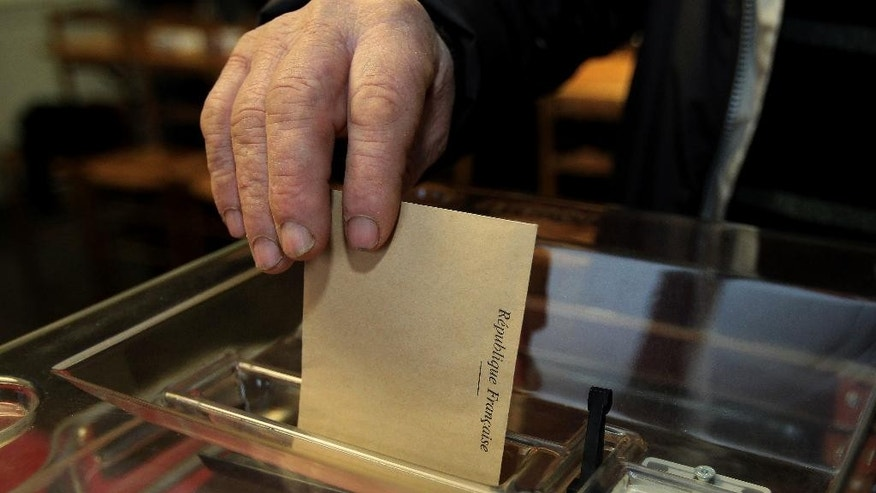 A man places his ballot , during the first round of local elections, in Sare, southwestern France, Sunday, March 22, 2015.  French voters are choosing local officials in elections on March 22 and March 29 that are expected to bring even more power to the increasingly popular far right National Front party. (AP Photo/Bob Edme)