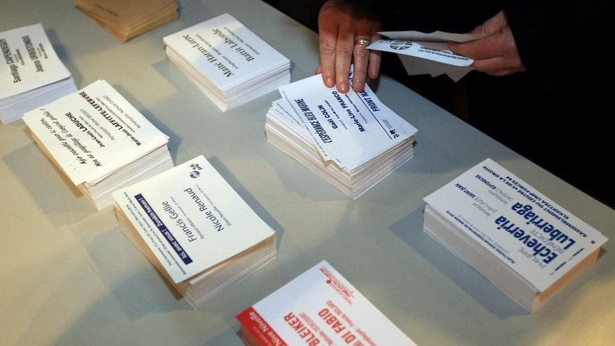 A person looks at leaflets from different parties, during the first round of local elections, in Sare, southwestern France, Sunday, March 22, 2015.  French voters are choosing local officials in elections on March 22 and March 29 that are expected to bring even more power to the increasingly popular far right National Front party. (AP Photo/Bob Edme)