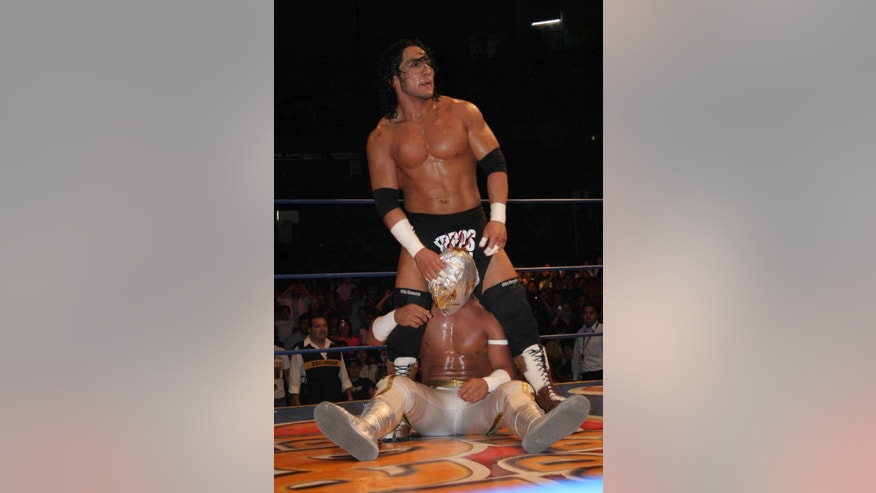 In this April 13, 2007 photo, Mexican wrestler Pedro Aguayo Ramirez, known as Hijo del Perro Aguayo, top, tries to remove the mask of Mistico during a wrestling match in Mexico City. Ramirez, the son of a wrestling legend in the country, died early Saturday March 21, 2015, from a hit suffered in the ring in Tijuana, the Baja California state prosecutor's office said. (AP Photo/Ezequiel Tlaxcala-CUARTOSCURO.COM) MEXICO OUT - NO PUBLICAR EN MEXICO - MANDATORY CREDIT - CREDITO OBLIGATORIO