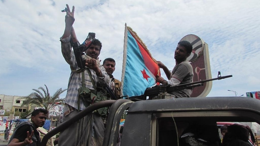 In this photo taken on Friday, March 20, 2015, militiamen loyal to President Abed Rabbo Mansour Hadi ride on an army vehicle on a street in Aden, Yemen. One of them holds a representation of the old South Yemen flag that was used when southern Yemen was an independent state until 1990. The country's Shiite rebels issued a call to arms Saturday to battle forces loyal to the embattled President Hadi, as U.S. troops evacuated a southern air base over al-Qaida militants seizing a nearby city, authorities said. (AP Photo/Yassir Hassan)