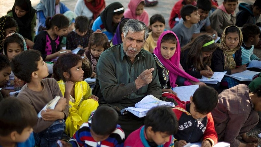 In this Wednesday, March 18, 2015 photo, Mohammed Ayub, a 57-year-old government worker, sits among students from poor families at a makeshift school set up in a park in Islamabad, Pakistan. Ayub has dedicated most of his life to teaching the less fortunate of this city. For three decades, children who might otherwise have gotten no education sat through his classes. (AP Photo/B.K. Bangash)