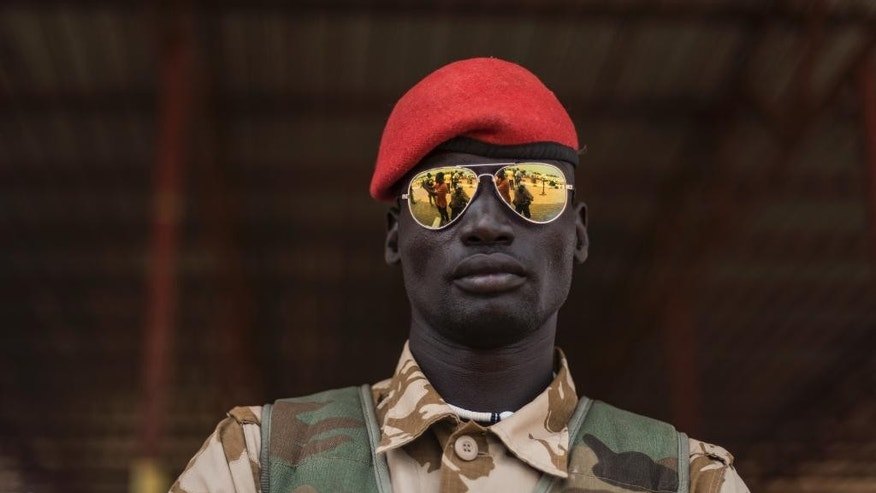 In this photo taken Tuesday, Feb. 24, 2015, a government soldier stands in the oil-rich town of Malakal, South Sudan. Hit by falling oil revenues, South Sudan's economy is also troubled by a violent conflict that looks set to continue and it could get worse for this young country, with the U.N. warning that South Sudan's economy is now threatened by rampant inflation as the central bank is allegedly printing money to meet a budget shortfall. (AP Photo/Jacob Zocherman)