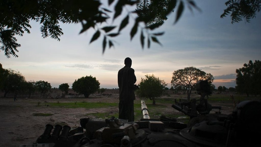 In this photo taken Wednesday, May 7, 2014, a rebel soldier stands guard on a tank at dusk in Leer, South Sudan. Hit by falling oil revenues, South Sudan's economy is also troubled by a violent conflict that looks set to continue and it could get worse for this young country, with the U.N. warning that South Sudan's economy is now threatened by rampant inflation as the central bank is allegedly printing money to meet a budget shortfall. (AP Photo/Jacob Zocherman)