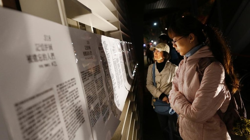 "Visitors read accounts of the 2014 student-led ""Sunflower Movement"" as protesters gather outside the parliament to mark the movement's first anniversary where student groups stormed the parliament grounds in Taipei, Taiwan, Sunday, March 22, 2015. About 300 university students gathered outside Taiwan's legislative house Sunday evening, kicking off a scheduled 31-hour demonstration to mark the anniversary of a movement that occupied the island's parliament. (AP Photo/Wally Santana)"