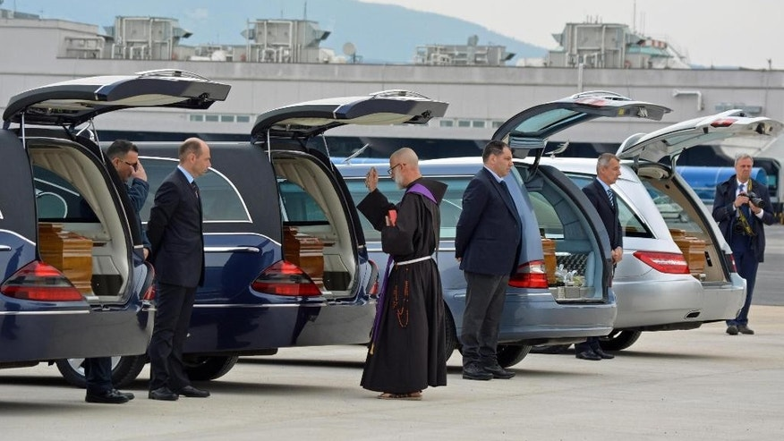 A priest blesses the coffins of the Italian victims of Tunis' National Bardo museum attack as the bodies of the four Italians who were killed in the attack arrived at the Ciampino airport near Rome, Saturday, March 21, 2015. (AP Photo/Telenews, Ansa)