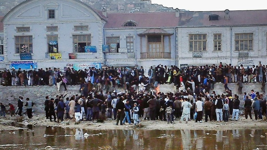 In this Thursday, March 19, 2015 photo, Afghan men gather around the body of 27-year-old Farkhunda, an Afghan woman who was beaten to death by a mob, as her body is set on fire in Kabul, Afghanistan. Hundreds of people gathered in northern Kabul for the funeral of Farkhunda on Sunday, who like many Afghans is known by only one name. Afghan women's rights activists dressed head-to-toe in black broke with tradition to carry the coffin of the woman in the capital over allegations she had burned a Quran. (AP Photo/Dilagha Rezai)