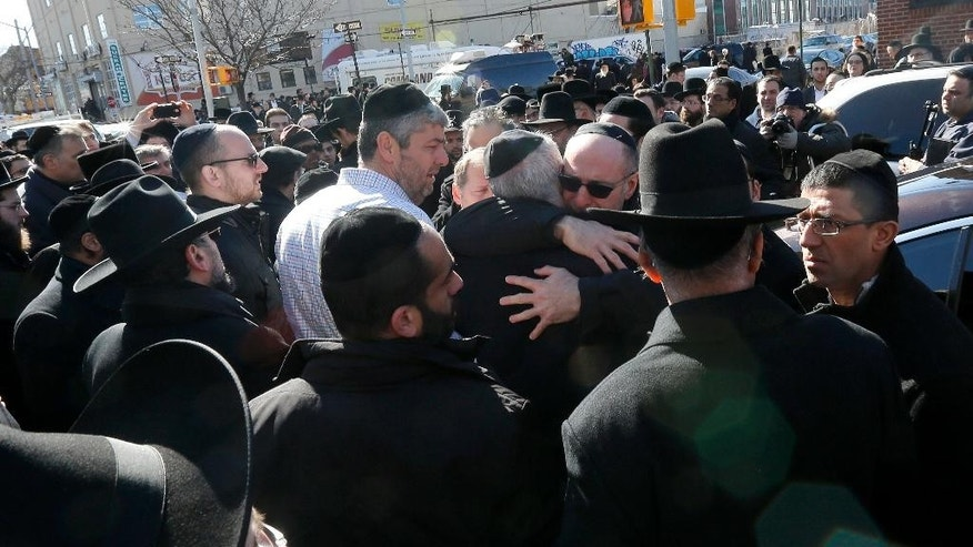 Mourners embrace each other after funeral services for the seven siblings killed in a house fire, Sunday, March 22, 2015, in the Brooklyn borough of New York. The siblings, ages 5 to 16, died early Saturday when flames engulfed the Sassoon family home in the Midwood neighborhood of Brooklyn. Investigators believe a hot plate left on a kitchen counter set off the fire that trapped the children and badly injured their mother and another sibling. (AP Photo/Julio Cortez)