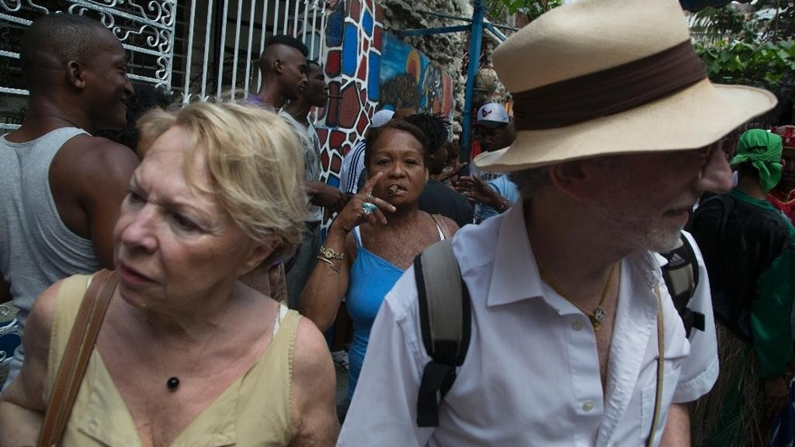 Tourists visit the Hamel Alley as a Cuban woman smokes a cigar in the background, in Havana, Cuba, Sunday, March 22, 2015. Tourism to Cuba is up sharply in the months since Washington and Havana announced in December that they would move toward a historic rapprochement. Where foreigners see charming, historic architecture, bright 1950s-era American cars and vast stretches of white-sand beaches, locals see decaying buildings in need of repair, new vehicles priced beyond their reach and a lack of economic opportunity. (AP Photo/Desmond Boylan)