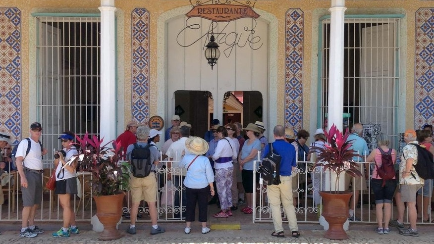 In this Feb. 25, 2015 photo, tourists look for souvenirs at a shop in Trinidad, southern Cuba. The sense that detente will unleash an invasion of Yankee tourists and change the unique character of one of the world's last remaining bastions of communism is shared by many travelers flocking here. (AP Photo/Enric Martí)