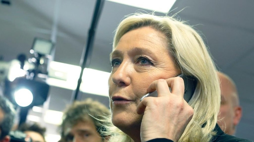 French far-right leader and National Front Party, Marine Le Pen speaks on the phone after a news conference at party headquarters, Sunday, March 22, 2015, in Nanterre, western France. For Le Pen, today's election for more than 2,000 local councils is an important step in building a grassroots base critical to her ultimate goal: the 2017 presidency. Local elections takes place today and the second round on March 29. (AP Photo/Jacques Brinon)