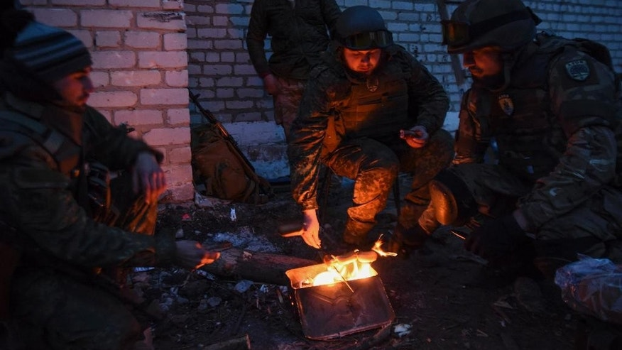 Fighters of the Azov Battalion cook food during a break in the town of Shyrokyne, eastern Ukraine, Sunday, March 22, 2015.  Government and Russian-backed separatist forces face off against one another across an unseen line cutting through the town in daily gun and artillery battles. The truce announced in mid-February never made it here. (AP Photo/Mstyslav Chernov)
