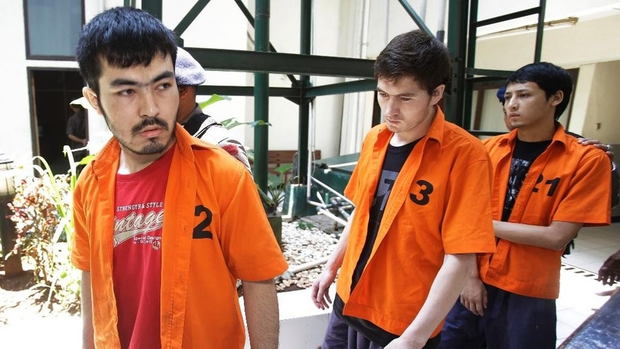 Alleged members of China's ethnic Uighur minority, from left to right, Abdulbasit Tuzer, Abdullah alias Altinci Bayyram and Ahmet Mahmud walk toward the courtroom prior to the start of their trial hearing at North Jakarta District Court in Jakarta, Indonesia, Monday, March 23, 2015. An Indonesian court has opened the trial of the four members, including them,  charged with involvement in terrorism activities and using fake passports. Ahmet Mahmud, Abdullah alias Altinci Bayyram, Abdulbasit Tuzer, and Ahmet Bozoglan, were arrested in September while trying to meet Indonesia's most wanted extremist Abu Wardah Santoso in Central Sulawesi. (AP Photo/Achmad Ibrahim)