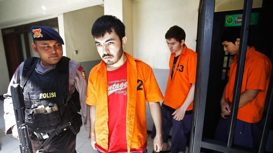 A police officer escorts alleged members of China's ethnic Uighur minority, from left to right, Abdulbasit Tuzer,  Abdullah alias Altinci Bayyram and Ahmet Mahmud walk toward the courtroom prior to the start of their trial hearing at North Jakarta District Court in Jakarta, Indonesia,  Monday, March 23, 2015. An Indonesian court has opened the trial of four alleged members, including them,  charged with involvement in terrorism activities and using fake passports. (AP Photo/Achmad Ibrahim)