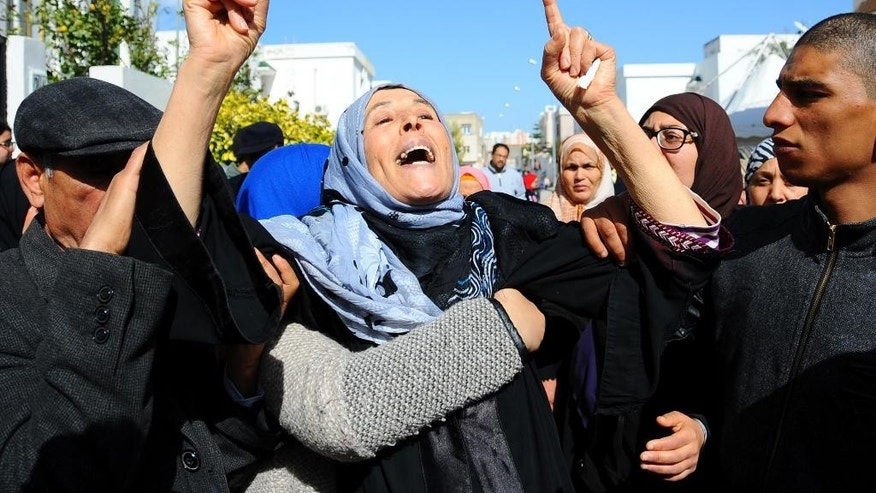Fatma Laabidi, mother of victim Yassine Laabidi, gestures as her son's coffin is transported from his home, in Jallez Cemetery, prior to his funeral, in Tunis, Sunday, March 22, 2015. The two extremist gunmen who killed 21 people at a museum in Tunis trained in neighboring Libya before caring out the deadly attack, a top Tunisian Security official said. (AP Photo/Salah Ben Mohamed)