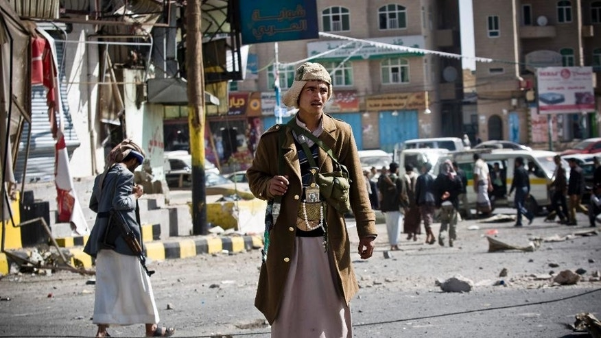 FILE - In this Tuesday, Jan. 20, 2015 file photo, Houthi Shiite Yemenis gather while guarding a street leading to the presidential palace in Sanaa, Yemen. The Shiite rebels, known as Houthis, captured the airport and city of Taiz -- a gateway to the south -- and have vowed to press on to Aden, the country's economic hub, where President Abed Rabbo Mansour Hadi, a close U.S. ally, has taken refuge. (AP Photo/Hani Mohammed, File)