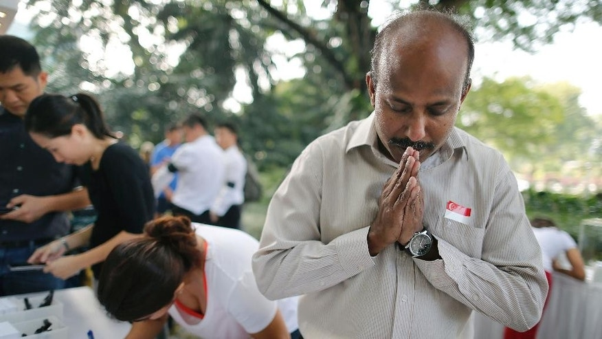 "Gunasegaran S., 51, from Singapore prays quietly while other members of the public write condolence messages outside the Istana, or presidential palace, Monday, March 23, 2015, in Singapore. Singaporeans wept and world leaders paid tribute Monday as the Southeast Asian city-state mourned the death of its founding father Lee Kuan Yew. The government announced that Lee, 91, ""passed away peacefully"" several hours before dawn at Singapore General Hospital. (AP Photo/Wong Maye-E)"