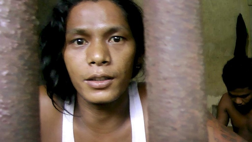"In this Thursday, Nov. 27, 2014 image from video, Kyaw Naing, a slave from Myanmar, looks through the bars of a cell at the compound of a fishing company in Benjina, Indonesia. After working for three years on a Thai trawler, sometimes enduring beatings with the bones of sting ray, he begged his captain to let him return home. ""All I did was tell my captain I couldn't take it anymore, that I wanted to go home,"" Naing says. ""The next time we docked, I was locked up."" (AP Photo/APTN)"