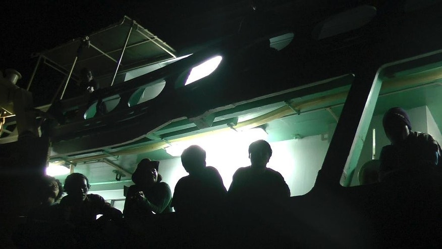 "In this Wednesday, Nov. 26, 2014 image from video, slaves from Myanmar lean over the deck of their fishing trawler at the port in Benjina, Indonesia. ""I want to go home. We all do,"" one man called out in Burmese, a cry repeated by others. ""Our parents haven't heard from us for a long time. I'm sure they think we are dead."" (AP Photo/APTN)"