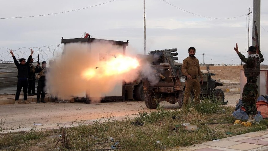 Imam Ali Brigades, members of of an Iraqi Shiite militant group,  launch rockets against Islamic State extremist positions during clashes in Tikrit, 130 kilometers (80 miles) north of Baghdad, Iraq, Tuesday, March 24, 2015. (AP Photo/Khalid Mohammed)