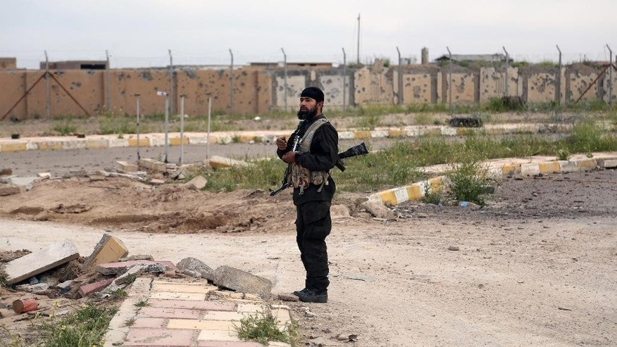 A member of an Iraqi Shiite militant group called Imam Ali Brigades stands guard in Tikrit, 130 kilometers (80 miles) north of Baghdad, Iraq, Tuesday, March 24, 2015. (AP Photo/Khalid Mohammed)