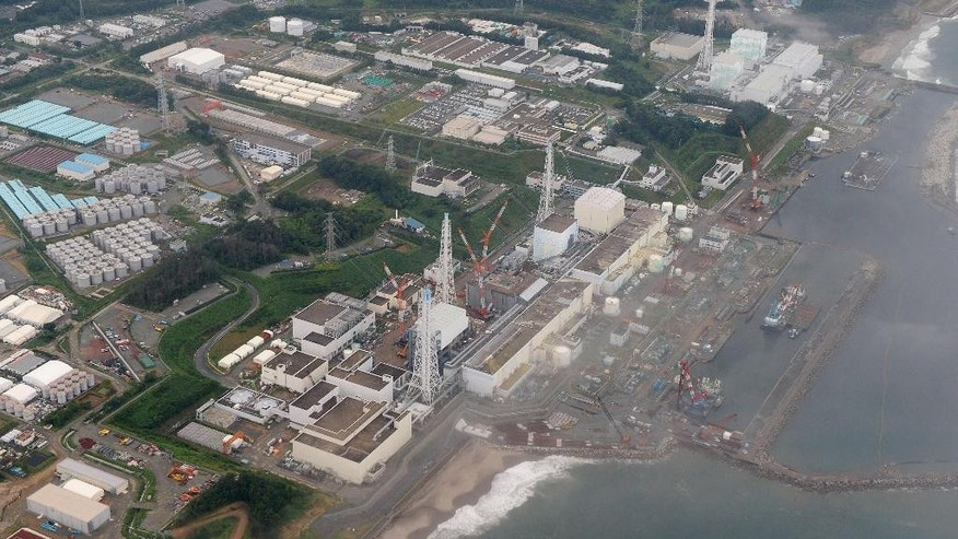 FILE - This Aug. 20, 2013 aerial file photo shows the Fukushima Dai-ichi nuclear plant at Okuma town in Fukushima prefecture, northeastern Japan. Japanese government auditors said the operator of the nuclear plant has wasted more than a third of the 190 billion yen ($1.6 billion) in taxpayer money allocated for cleaning up the plant after it was destroyed by a March 2011 earthquake and tsunami. A Board of Audit report describes various expensive machines and untested measures that ended in failure. It also says the cleanup work has been dominated by one group of Japanese utility, construction and electronics giants despite repeated calls for more transparency and greater access for international bidders. (AP Photo/Kyodo News, File) JAPAN OUT, MANDATORY CREDIT