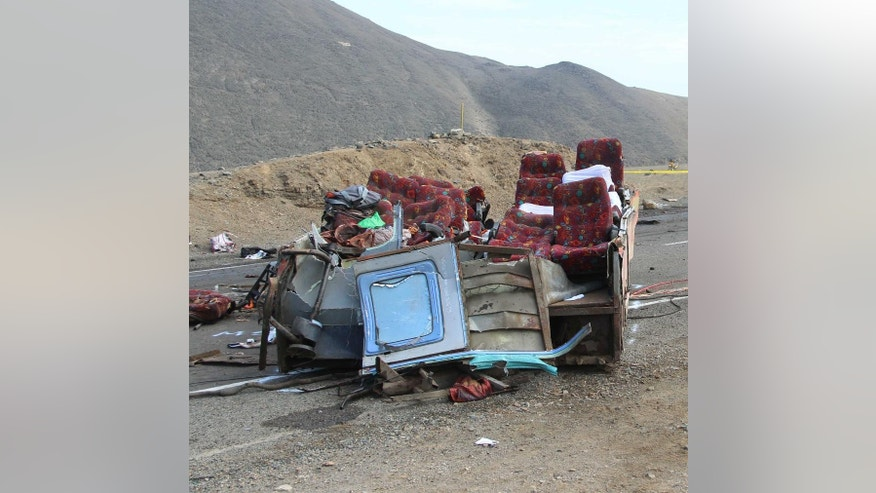 The rubble of a passenger bus lays on a coastal highway after a multiple vehicle collision in Huarmey, Peru, Monday, March 23, 2015. Monday's pre-dawn crash involving buses and a truck killed dozens of people and injured dozens more. Police say a bus strayed into the oncoming lane and slammed head-on into the first of two other buses. A truck then plowed into the wreckage. (AP Photo/Magali Estrada)