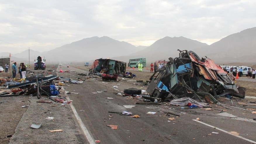 The rubble of crashed vehicles litters a coastal highway in Huarmey, Peru, Monday, March 23, 2015. Monday's pre-dawn crash involving buses and a truck killed dozens of people and injured dozens more. Police say a bus strayed into the oncoming lane and slammed head-on into the first of two other buses. A truck then plowed into the wreckage. (AP Photo/Magali Estrada)
