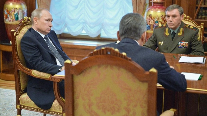 Russian President Vladimir Putin, left, meets with Chief of the General Staff of the Russian Armed Forces Valery Gerasimov, back, and Defense Minister Sergei Shoigu, front, in the Kremlin in Moscow, Russia, Tuesday, March 24, 2015. (AP Photo/RIA-Novosti, Alexei Druzhinin, Presidential Press Service)
